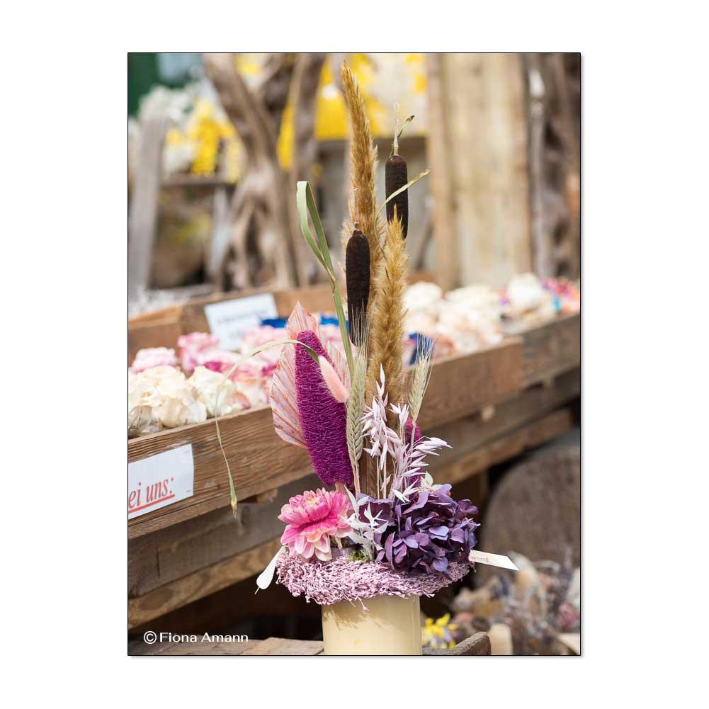 Kleines Gesteck aus konservierten Blumen. Im Hintergrund einzelne konservierte Blüten.